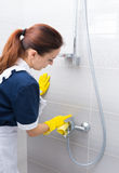 Housekeeper cleaning the fittings in a shower Stock Image