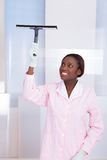 Housekeeper Cleaning Glass In Hotel. Smiling African American housekeeper cleaning glass in hotel Royalty Free Stock Image