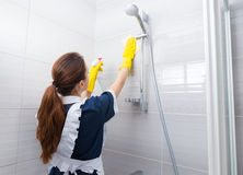 Housekeeper cleaning the shower head. In the bathroom reaching up to wipe it as she sprays it with detergent, rear view Royalty Free Stock Images