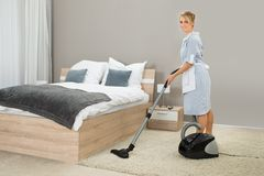 Housekeeper cleaning with vacuum cleaner Royalty Free Stock Images