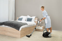Housekeeper Cleaning With Vacuum Cleaner Royalty Free Stock Image