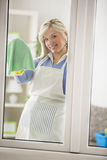 Housekeeper cleaning window Stock Photo