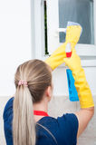 Housekeeper cleaning window with rag and detergent spray Stock Photo