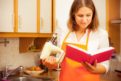 Housekeeper with cookbook and mixer Stock Photo
