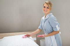 Housekeeper decorating bed with petals Stock Image