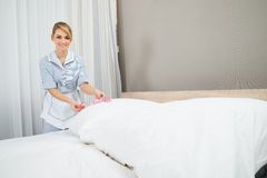 Housekeeper decorating bed with petals Royalty Free Stock Photography