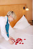 Housekeeper Decorating Bed With Petals Royalty Free Stock Photos
