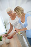 Housekeeper and elderly woman at home. Housekeeper cleaning elderly woman's home Royalty Free Stock Images