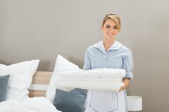Housekeeper holding stack of sheet. Young Female Housekeeper Holding Stack Sheet In Hotel Room Stock Photography
