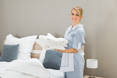 Housekeeper Holding Stack Of Sheet. Young Female Housekeeper Holding Stack Sheet In Hotel Room Stock Images