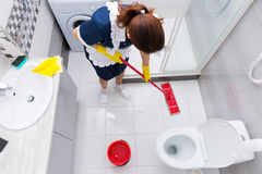 Housekeeper in a hotel mopping a floor. In a clean white bathroom with a mop, view from above Stock Photos