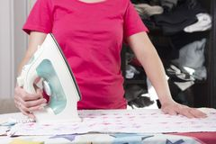 Housekeeper with iron and clothes near ironing board. Housework. servant strokes things out of closet. Royalty Free Stock Photos