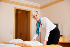 Housekeeper Keeping Bathrobe On Bed Stock Images