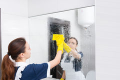 Housekeeper or maid cleaning a large wall mirror. In a white bathroom wiping it with a cloth after spraying it with detergent stock images
