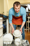 Housekeeper man with dish washing. Positive happy housekeeper at kitchen work with dish washing machine Royalty Free Stock Photography