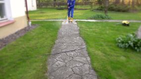 Housekeeper man washing concrete path near his house. stock video