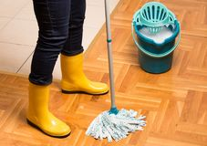 Housekeeper mopping parquet floor. Maid in gumboots mopping parquet floor. Housekeeping and home hygiene concept Royalty Free Stock Image