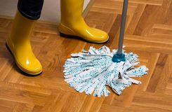 Housekeeper mopping parquet floor. Maid in gumboots mopping parquet floor. Housekeeping and home hygiene concept Stock Photography