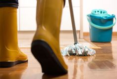 Housekeeper mopping tiled floor. Maid in gumboots mopping tiled floor in kitchen. Housekeeping and home hygiene concept Stock Image
