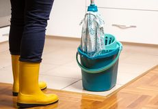 Housekeeper mopping tiled floor. Maid in gumboots mopping tiled floor in kitchen. Housekeeping and home hygiene concept Stock Photo