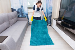 Housekeeper replacing and positioning a rug Stock Photography