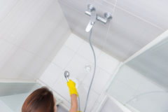 Housekeeper rinsing the white tiles on a shower Stock Photo