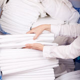 Housekeeper's Hands Stacking Sheet. Closeup of female housekeeper's hands stacking sheet in stock room Royalty Free Stock Images