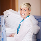 Housekeeper Stacking Sheets In Stock Room Royalty Free Stock Image