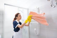 Housekeeper straightening towel in bathroom Stock Photos