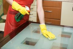 Housekeeper washing glass table in with cleaning spray and sponge wearing gloves in apartment.  Stock Photo