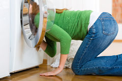Housekeeper with washing machine. Young woman or housekeeper has a laundry day at home, she is searching for the lost socks Stock Image