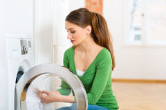 Housekeeper with washing machine. Young woman or housekeeper has laundry day at home, she takes the out of the washing machine or the dryer Stock Image