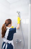 Housekeeper wiping the shower fixtures Royalty Free Stock Images