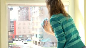 Housekeeper woman clean window with rag at home. stock video