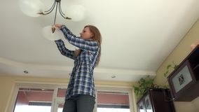 Housekeeper woman climb up and change light bulbs in chandelier. Pretty housekeeper woman climb up and change light bulbs in chandelier stock footage