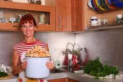 Housekeeping!. A smiling woman holding a saucepan with mushrooms stands in the kitchen Royalty Free Stock Images