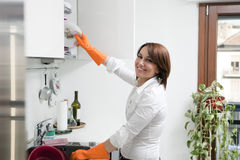 Housekeeping. Side view of young woman in kitchen doing housekeeping royalty free stock photography