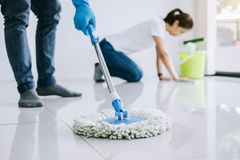 Housekeeping and cleaning concept, Young couple in blue rubber g. Loves wiping dust using mop and duster while helping cleaning on floor at home royalty free stock photography