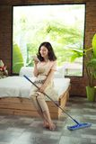 Housekeeping concept. Woman texting while doing housework royalty free stock photos