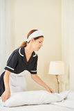 Housekeeping maid making bed in hotel room. Housekeeping maid in uniform making bed in a hotel room Stock Photo