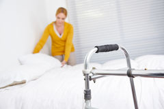 Housekeeping in nursing home. Cleaning lady doing housekeeping in nursing home with walker in front royalty free stock photos