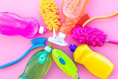 Housekeeping set. Detergents, soap, cleaners and brush for housecleaning on pink background top view mock-up.  royalty free stock photo