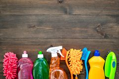 Housekeeping set. Detergents, soap, cleaners and brush for housecleaning on wooden background top view mock-up.  stock photography