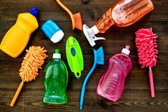 Housekeeping set. Detergents, soap, cleaners and brush for housecleaning on wooden background top view mock-up.  royalty free stock photo