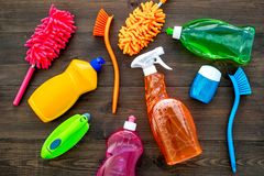 Housekeeping set. Detergents, soap, cleaners and brush for housecleaning on wooden background top view mock-up royalty free stock photo