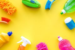 Housekeeping set. Detergents, soap, cleaners and brush for housecleaning on yellow background top view mock-up royalty free stock image