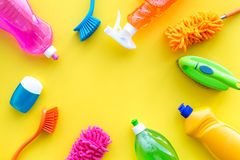 Housekeeping set. Detergents, soap, cleaners and brush for housecleaning on yellow background top view mock-up.  stock photo