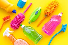 Housekeeping set. Detergents, soap, cleaners and brush for housecleaning on yellow background top view mock-up.  stock images