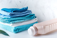 Housekeeping set with towels and plastic bottles on laundry background Stock Photo