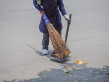 Housekeeping staff Sweeping leaves. Royalty Free Stock Image